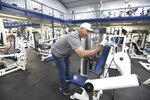 Larry Danko wipes down a workout seat at his business Monday morning, May 25, 2020 in Plains, Pa. After being shut down since March, Larry Danko defied a state order and reopened his fitness center in Plains Twp. at 5 a.m. Tuesday morning even though Luzerne County remains in the red phase. Police and state regulators are cracking down on a handful of Pennsylvania businesses that are supposed to remain shut down during the pandemic but have instead thrown open their doors. (Mark Moran/The Citizens' Voice via AP)