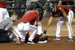 Arizona Diamondbacks' Steven Souza Jr. lies on the field and is assisted after getting injured while scoring against the Chicago White Sox in the fourth inning of a spring training baseball game Monday, March 25, 2019, in Phoenix, Ariz. (AP Photo/Elaine Thompson)