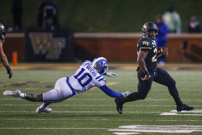 Wake Forest running back Kenneth Walker III, right, avoids Duke safety Marquis Waters (10) in the second half of an NCAA college football game in Winston-Salem, N.C., Saturday, Nov. 23, 2019. Wake Forest won 39-27. (AP Photo/Nell Redmond)
