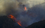 In this Wednesday, Sept. 12, 2018, photo hot spots flare up near a rock formation a wildfire burns in northern Juab County, Utah. A fast-moving Utah wildfire fanned by high-winds has more than doubled in size as it burns through dry terrain and forces evacuations of hundreds of homes, the U.S. Forest Service said Friday. (Isaac Hale/The Daily Herald via AP)
