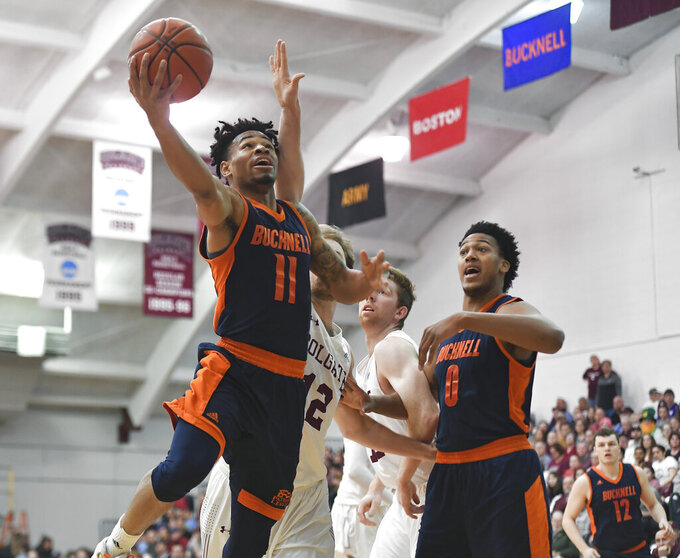 Bucknell guard Avi Toomer, left, drives for a layup past Colgate center Dana Batt as Bucknell center Paul Newman (0) watches during the first half of an NCAA college basketball game for the championship of the Patriot League men's tournament in Hamilton, N.Y., Wednesday, March 13, 2019. (AP Photo/Adrian Kraus)