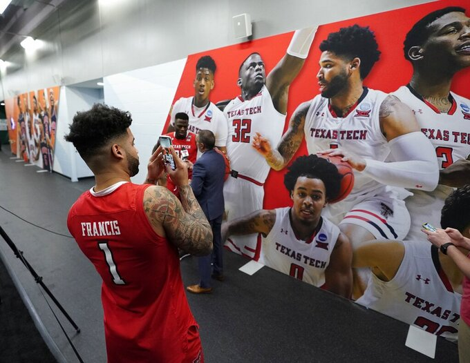 Texas Tech's Brandone Francis takes a picture of his picture after a practice session for the semifinals of the Final Four NCAA college basketball tournament, Thursday, April 4, 2019, in Minneapolis. (AP Photo/David J. Phillip)