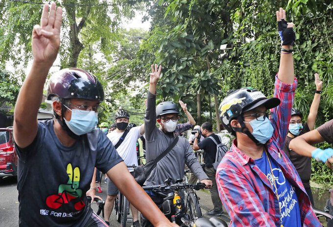 Activists ride their bicycles as they flash a three-finger salute of defiance during a rally called 'bike for Myanmar' against the military coup in Jakarta, Indonesia, Saturday, April 24, 2021. Southeast Asian leaders met Myanmar's top general and coup leader in an emergency summit in Indonesia Saturday, and are expected to press calls for an end to violence by security forces that has left hundreds of protesters dead as well as the release of Aung San Suu Kyi and other political detainees. (AP Photo/Tatan Syuflana)