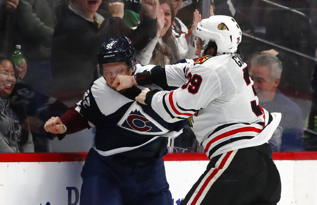 Chicago Blackhawks defenseman Dennis Gilbert, right, connects with a pujch to the face of Colorado Avalanche left wing Gabriel Landeskog during the second period of an NHL hockey game Saturday, Dec. 21, 2019, in Denver. (AP Photo/David Zalubowski)