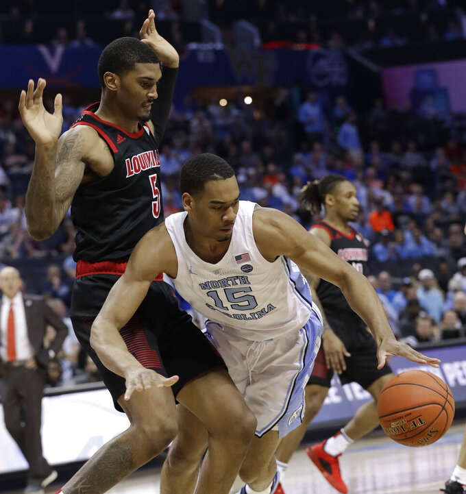 North Carolina's Garrison Brooks (15) is tripped by Louisville's Malik Williams (5) during the first half of an NCAA college basketball game in the Atlantic Coast Conference tournament in Charlotte, N.C., Thursday, March 14, 2019. Brooks was injured on the play but returned to the game. (AP Photo/Chuck Burton)