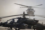 A Blackhawk helicopter lands next to an Apache attack helicopter at a U.S. military base at undisclosed location in Eastern Syria, Monday, Nov. 11, 2019.  A senior U.S. coalition commander said Friday, Nov. 15,  the partnership with Syrian Kurdish forces remains strong and focused on fighting the Islamic State group, despite an expanding Turkish incursion on areas of Kurdish control. (AP Photo/Darko Bandic)