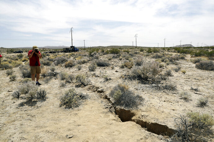 FILE - In this July 7, 2019 file photo, a visitor takes a photo of a crack in the ground following recent earthquakes in Ridgecrest, Calif., near the Naval Air Weapons Station China Lake military base. The base sustained heavy damage that experts estimate will cost nearly $5 billion to repair. (AP Photo/Marcio Jose Sanchez, File)