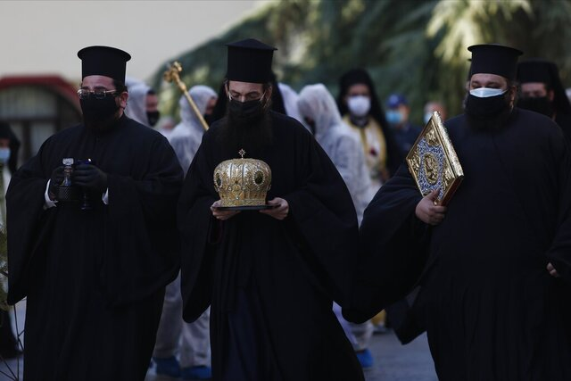 Priests wearing face masks to protect against the spread of the coronavirus, attend the funeral of senior clergyman Ioannis of Lagadas after he died of COVID-19,  in Greece's Orthodox Church, in the northern city of Thessaloniki, Greece, Monday, Nov. 16, 2020. Metropolitan Bishop Ioannis of Lagadas, 62, was an outspoken advocate of maintaining communion ceremonies _ at which worshipers are given bread as well as wine with a shared spoon _ during the pandemic, arguing that there was no risk of transmission.  (AP Photo/Giannis Papanikos)