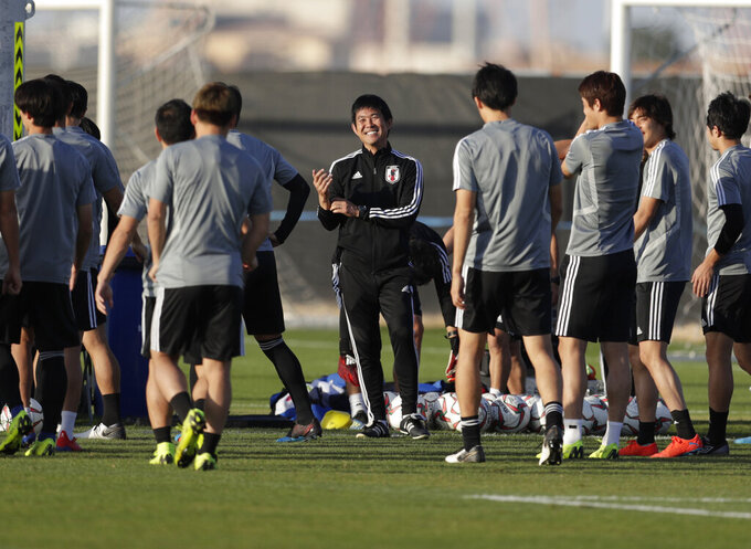 FILE - In this Jan. 31, 2019, file photo, Japan coach Hajime Moriyasu, center, laughs as gives instructions to his players during training session in the Cricket training site on the eve of the AFC Asian Cup final match between Qatar and Japan in Abu Dhabi, United Arab Emirates. Even though men's soccer squads at this Olympics are mostly players under the age of 24, Japan is not using a youth team coach for the Olympics. Moriyasu, who has been in charge of the senior team since 2018, will coach at the Olympics as well. (AP Photo/Hassan Ammar, File)