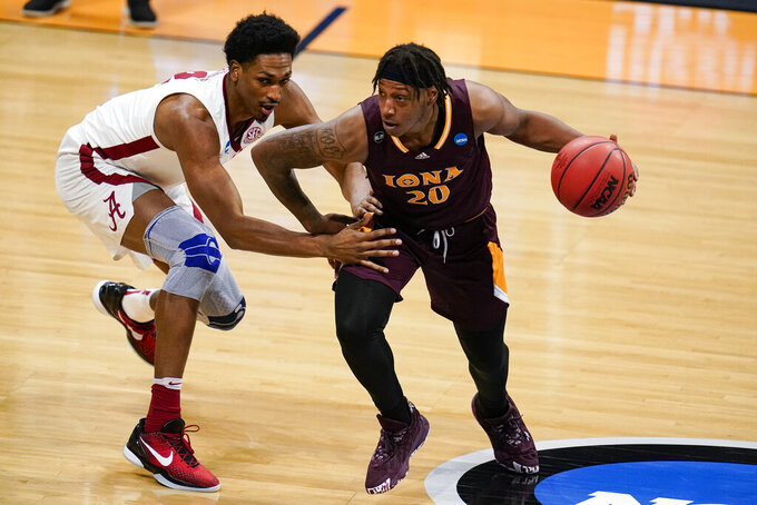 Iona guard Isaiah Ross (20) drives on Alabama forward Jordan Bruner (2) in the first half of a first-round game in the NCAA men's college basketball tournament at Hinkle Fieldhouse in Indianapolis, Saturday, March 20, 2021. (AP Photo/Michael Conroy)