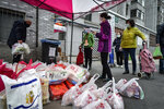 In this Saturday, Feb. 22, 2020, photo, residents wearing protective face masks collect foods distributed by volunteers outside their home in Wuhan in central China's Hubei province. South Korea and China both reported a rise in new virus cases on Sunday, as the South Korean prime minister warned that the fast-spreading outbreak linked to a local church and a hospital in the country's southeast had entered a