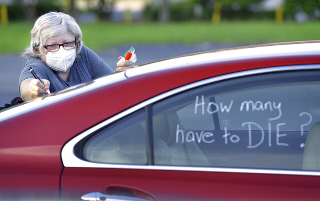 Registered Nurse Laure Hale writes on her car as she is preparing to take part in a motorcade protest to the Duval County School Board building, Tuesday, July 14, 2020 in Jacksonville, Fla. Duval County teachers and their supporters gathered in a parking lot before they drove to the Duval County School Board Building and protest plans of starting the upcoming school year with the rate of COVID-19 infections hitting record rates in Jacksonville. (Bob Self/The Florida Times-Union via AP)