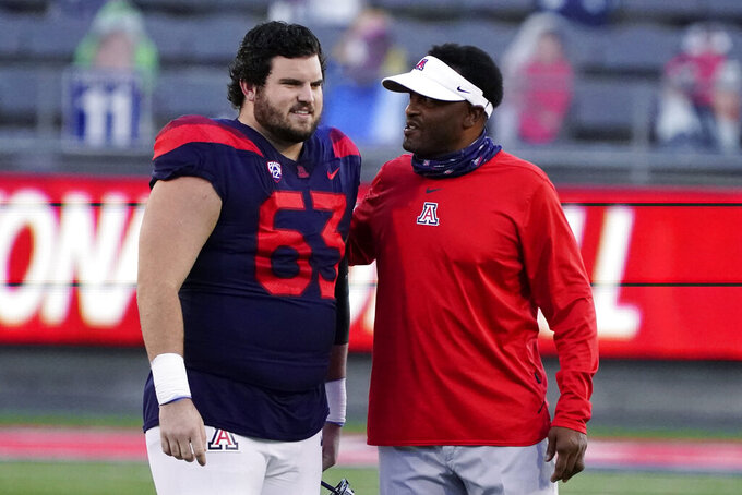 Arizona head coach Kevin Sumlin talks to Steven Bailey (63) before the team's NCAA college football game against Arizona State, Friday, Dec. 11, 2020, in Tucson, Ariz. Arizona fired Sumlin on Saturday, Dec. 12, a day after a 70-7 loss to Arizona State extended the Wildcats' losing streak to a record 12 games over two seasons.(AP Photo/Rick Scuteri)