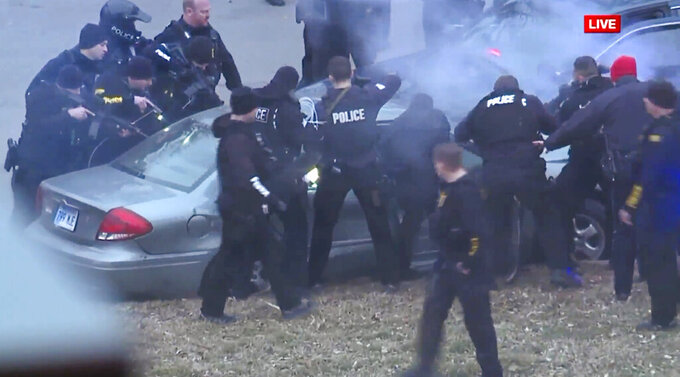 In this image take from video, law enforcement personnel surround a car after it was stopped as the driver approached the crowd near Union Station attending the Super Bowl parade and rally for the Kansas City Chief in Kansas City, Mo., Wednesday, Feb. 5, 2020. (FOXKC via AP)