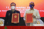 In this handout photo provided by the Department of National Defense Public Affairs Office (PAO), Philippine Defense Secretary Delfin N. Lorenzana, right, poses beside his Chinese counterpart General Wei Fenghe after the signing ceremony for donations in Humanitarian Assistance and Disaster Relief equipment from China at the Department of National Defense in Quezon city, Philippines, Friday Sept. 11, 2020. (Department of National Defense PAO via AP)