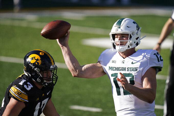 Michigan State quarterback Rocky Lombardi (12) throws a pass over Iowa defensive end Joe Evans (13) during the second half of an NCAA college football game, Saturday, Nov. 7, 2020, in Iowa City, Iowa. Iowa won 49-7. (AP Photo/Charlie Neibergall)