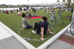 People sit inside circles marked on the grass for proper social distancing as they relax in Brooklyn's Domino Park during the current coronavirus outbreak, Monday, May 18, 2020, in New York. The circles are a reminder to people to stay at least six feet from others after an episode of severe overcrowding just over a week ago during a spate of unseasonably warm weather. (AP Photo/Kathy Willens)