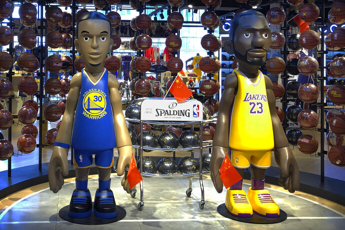 Statues of NBA players Stephen Curry of the Golden State Warriors, left, and Lebron James of the Los Angeles Lakers hold Chinese flags in the entrance of an NBA merchandise store in Beijing, Tuesday, Oct. 8, 2019. Chinese state broadcaster CCTV announced Tuesday it will no longer air two NBA preseason games set to be played in the country. (AP Photo/Mark Schiefelbein)