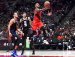 Portland Trail Blazers guard Damian Lillard, right, drives to the basket on Los Angeles Clippers forwards Danilo Gallinari, left, and Tobias Harris during the second half of an NBA basketball game in Portland, Ore., Thursday, Nov. 8, 2018. The Blazers won 116-105. (AP Photo/Steve Dykes)