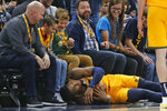 Utah Jazz guard Donovan Mitchell lays on the floor after going for a loose ball against the Minnesota Timberwolves in the first half during an NBA basketball game Monday, Nov. 18, 2019, in Salt Lake City. (AP Photo/Rick Bowmer)