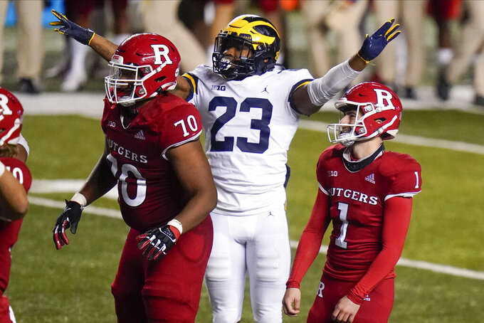 Rutgers' Valentino Ambrosio (1) and teammate Reggie Sutton (70) react as Michigan's Michael Barrett celebrates Ambrosio missing a field goal in overtime of an NCAA college football game Saturday, Nov. 21, 2020, in Piscataway, N.J. Michigan won 48-42. (AP Photo/Frank Franklin II)