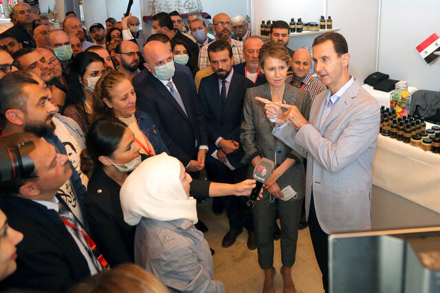 In this photo provided by the official Facebook page of the Syrian Presidency, Syrian President Bashar Assad, right, and first lady Asma Assad, center right, speaks with people during his visit to the Producers exhibition, in Damascus, Syria, Wednesday, Nov. 4, 2020. Assad said much of the current economic distress in Syria is a direct result of the banking crisis in neighboring Lebanon, where many Syrian businessmen have traditionally kept their money. He added that between $20 billion- and $ 42 billion held by Syrians were estimated to be stuck in Lebanese banks.(Syrian Presidency Facebook page via AP)