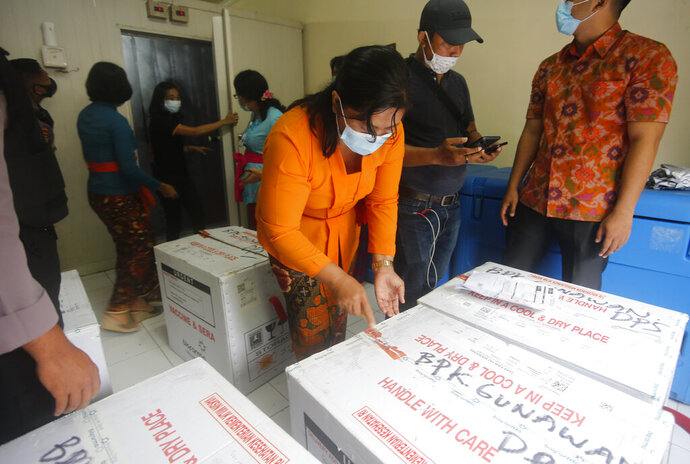 Health workers check the boxes containing coronavirus vaccines developed by China's Sinovac Biotech as they arrived in Bali, Indonesia on Thursday, Jan. 7, 2021. (AP Photo/Firdia Lisnawati)