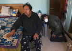 Ricardo Ledesma Carrasco, right, prepares a newly-refilled oxygen tank for his father Juan Jose Ledesma, 68, left, who is being treated for COVID-19 at home where he is isolating in Mexico City, Thursday, Dec. 31, 2020. (AP Photo/Marco Ugarte)
