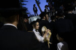 An Ultra-Orthodox Jewish youth holds a chicken during the Kaparot ritual in Bnei Brak, Israel, Monday, Oct. 7, 2019. Observant Jews believe the ritual transfers one's sins from the past year into the chicken, and is performed before the Day of Atonement, Yom Kippur, the holiest day in the Jewish year which starts at sundown Tuesday. (AP Photo/Oded Balilty)