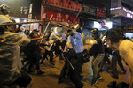 Policemen clash with demonstrators on a street during a protest in Hong Kong, Sunday, Aug. 25, 2019. Hong Kong police have rolled out water cannon trucks for the first time in this summer's pro-democracy protests. The two trucks moved forward with riot officers Sunday evening as they pushed protesters back along a street in the outlying Tsuen Wan district. (AP Photo/Kin Cheung)