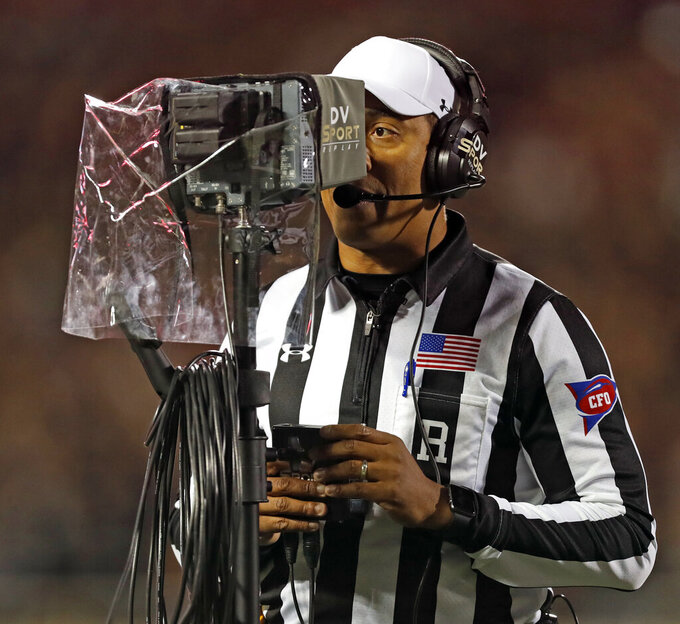 "FILE - In this Nov. 3, 2018, file photo, referee Reggie Smith reviews a targeting penalty during the first half of an NCAA college football game in Lubbock, Texas. The NCAA Playing Rules Oversight Panel adjusted the targeting rule in college football, allowing video review officials to overturn calls if any element of the penalty cannot be confirmed. The adjustment to the rule announced Tuesday, April 23, 2019, means there will be no option for letting the call on the field ""stand"" during a targeting review. It must either be confirmed or overturned. (AP Photo/Brad Tollefson, File)"