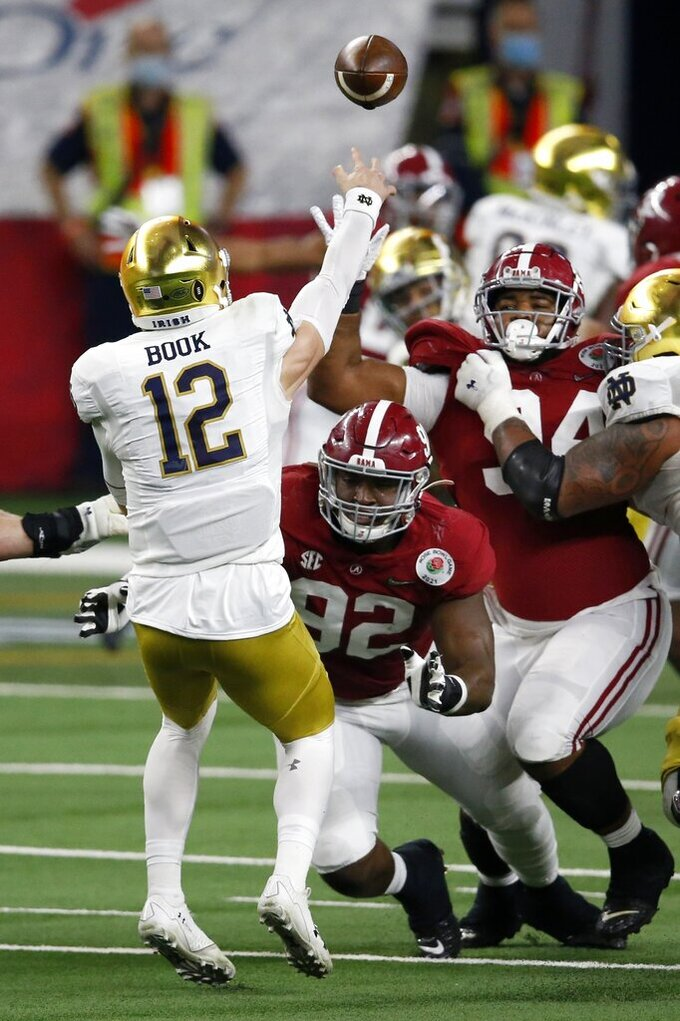 Notre Dame quarterback Ian Book (12) throws a pass under pressure from Alabama defensive lineman Justin Eboigbe (92) and defensive lineman DJ Dale (94) in the first half of the Rose Bowl NCAA college football game in Arlington, Texas, Friday, Jan. 1, 2021. (AP Photo/Roger Steinman)