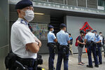 """Chen Baoying, right with red backpack, one of the four protesters is searched by police officers during a protest against an election committee in Hong Kong Sunday, Sept. 19, 2021. Hong Kong's polls for an election committee that will vote for the city's leader kicked off Sunday amid heavy police presence, with chief executive Carrie Lam saying that it is """"very meaningful"""" as it is the first election to take place following electoral reforms. (AP Photo/Vincent Yu)"""