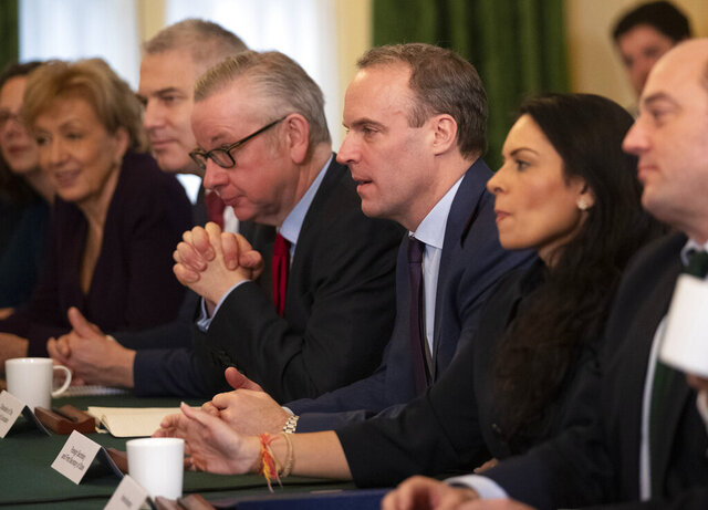FILE - In this file photo dated Tuesday, Dec. 17, 2019, Britain's Foreign Secretary Dominic Raab, 3rd right, Home Secretary Priti Patel, 2nd right, lawmaker Michael Gove, fourth left, listen as Britain's Prime Minister Boris Johnson speaks during his first cabinet meeting since the general election, inside 10 Downing Street in London.  With British Prime Minister Boris Johnson hospitalized and in intensive care Wednesday April 8, 2020, after contracting the new coronavirus, Raab, Gove and Patel are among key players in Johnson's Cabinet who will be directing Britain's response to the highly contagious COVID-19 coronavirus, while their leader is being treated. (AP Photo/Matt Dunham, FILE)