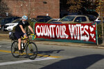 """FILE - In this Nov. 10, 2020, file photo, a bicyclist passes a """"Count Our Votes"""" sign near the Allegheny County Election Division Warehouse on Pittsburgh's Northside, where votes were continue to be counted from the Nov. 3, 2020 general election. A Republican proposal made public on Thursday, June 10, 2021, would revamp Pennsylvania election law to affect deadlines, early voting and mail-in ballots and require ID for all in-person voters. (AP Photo/Gene J. Puskar, File)"""