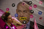 """An Israeli protester wears pink during a demonstration against Israeli Prime Minister Benjamin Netanyahu outside his official residence in Jerusalem, Saturday, June 12, 2021. If all goes according to plan, Israel will swear in a new government on Sunday, ending Prime Minister Benjamin Netanyahu's record 12-year rule and a political crisis that inflicted four elections on the country in less than two years. Hebrew reads: """"You failed"""","""" Israel free"""" and """"Leave"""". (AP Photo/Ariel Schalit)"""
