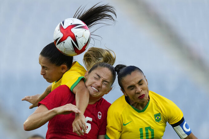 Brazil's Debinha, left, her teammate Marta, right, and Canada's Janine Beckie go for a header during a women's quarterfinal soccer match at the 2020 Summer Olympics, Friday, July 30, 2021, in Rifu, Japan. (AP Photo/Andre Penner)