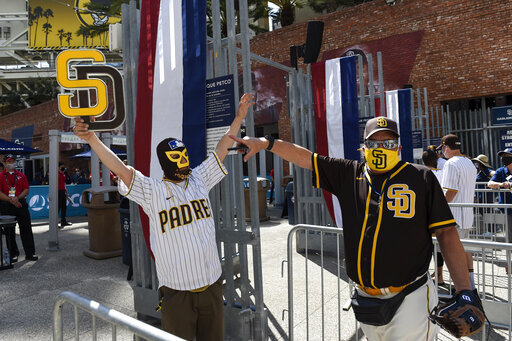 Baseball fans Mercury Hornbeek, left, and Steven Ames wait in line before the gates opened up before a baseball game between the Arizona Diamondbacks and the San Diego Padres Thursday, April 1, 2021, on opening day in San Diego. (AP Photo/Denis Poroy)