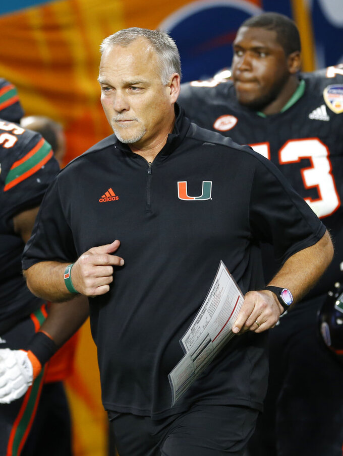 FILE - In this Dec. 30, 2017, file photo, Miami head coach Mark Richt enters the field during the second half of the Orange Bowl NCAA college football game against Wisconsin, in Miami Gardens, Fla. Some traditional recruiting heavyweights have plenty of work to do in the next several weeks to sign the level of talent they usually attract each year. As college football's early signing period concluded Friday, Southern California was outside the top 20 and Miami wasn't in the top 30 of the team standings in composite rankings of recruiting sites compiled by 247Sports. (AP Photo/Joe Skipper, File)