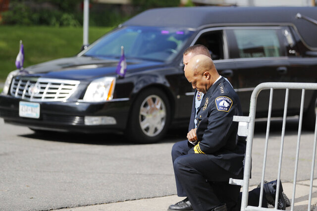 Police officers including Minneapolis Police Chief Medaria Arradondo, foreground, take a knee as the body of George Floyd arrives before his memorial services on Thursday, June 4, 2020 in Minneapolis. (AP Photo/Julio Cortez)
