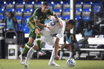 Portland Timbers midfielder Marvin Loria, left, is separated from the ball by LA Galaxy defender Daniel Steres (5) during the first half of an MLS soccer match Monday, July 13, 2020, in Kissimmee, Fla. (AP Photo/Phelan M. Ebenhack)