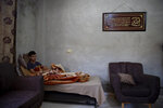Palestinian youth, Tareq Zubeidi, 15, rests at his house, in the West Bank village of Silat ad-Dhahr, Tuesday, Aug. 31, 2021. Zubeidi says he was abducted and beaten by a group of Israeli settlers after they found him and his friends eating snacks near an evacuated hilltop settlement in the occupied West Bank. More than two weeks after the Aug. 17 incident, he says he can barely walk and is afraid to leave his home. (AP Photo/Majdi Mohammed)