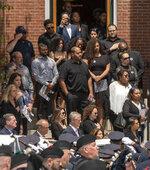 Mourners watch as the casket of fallen Worcester Police Officer Enmanuel Familia is carried from St. John Church after his funeral Mass in Worcester, Massachusetts Thursday, June 10, 2021. (Ashley Green/Worcester Telegram & Gazette via AP)
