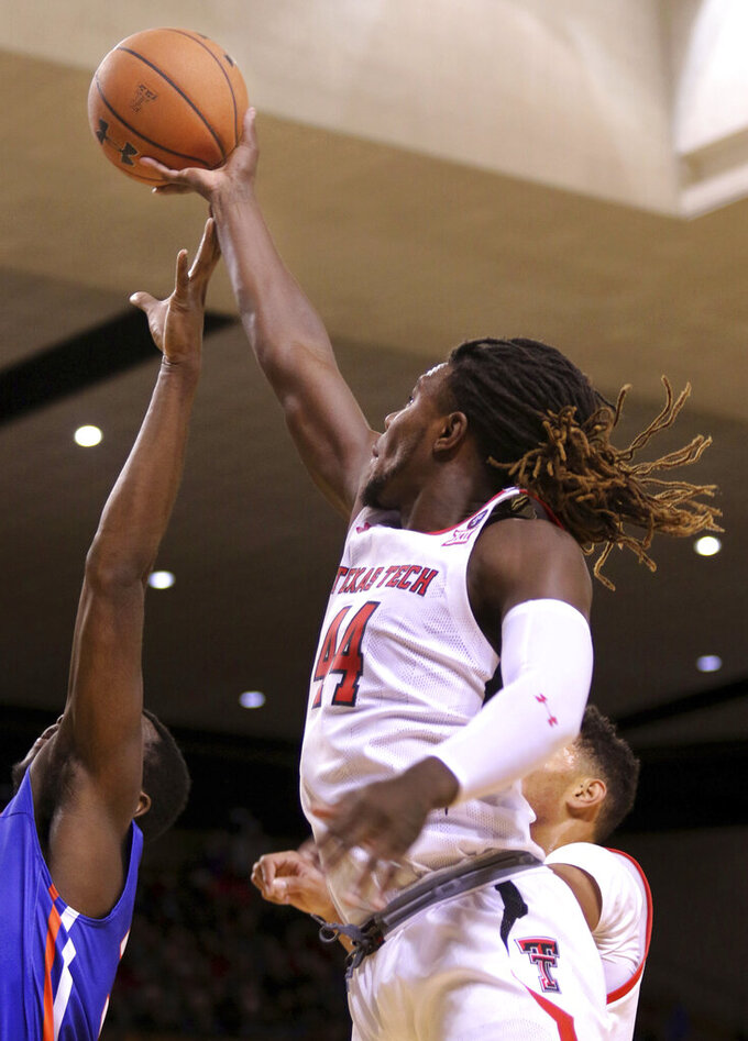 Texas Tech's Christ Clarke scores over Houston Baptist defender Benjamin Uloko, left, during an NCAA college basketball game Wednesday, Nov. 13, 2019, in Midland, Texas. (Ben Powell/Odessa American via AP)