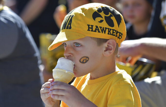 A young fan enjoys ice cream in the stands before the kickoff of an NCAA college football game between Iowa and Colorado State, Saturday, Sept. 25, 2021, in Iowa City, Iowa. (AP Photo/Ron Johnson)