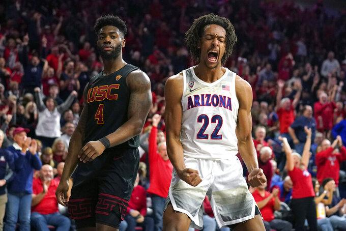 Arizona forward Zeke Nnaji (22) reacts after dunking next to Southern California guard Daniel Utomi during the second half of an NCAA college basketball game Thursday, Feb. 6, 2020, in Tucson, Ariz. Arizona won 85-80 (AP Photo/Rick Scuteri)