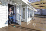 Steve O'Donnell exits his parent's flooded lake house in the Hanson's Lake area Friday, March 22, 2019, in Bellevue, Neb. Flooding in Nebraska has caused an estimated $1.4 billion in damage. The state received Trump's federal disaster assistance approval on Thursday. (Kent Sievers/Omaha World-Herald via AP)