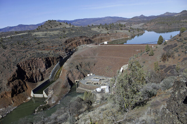 In this photo taken March 3, 2020, the Iron Gate Dam, powerhouse and spillway are on the lower Klamath River near Hornbrook, Calif. A plan to demolish four dams on California's second-largest river to benefit threatened salmon has sharpened a decades-old dispute over who has the biggest claim to the river's life-giving waters. The project, if it goes forward, would be the largest dam demolition project in U.S. history and would include the Iron Gate Dam facility pictured. (AP Photo/Gillian Flaccus)