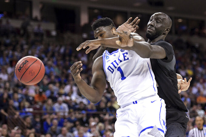 Central Florida center Tacko Fall (24) defends against Duke forward Zion Williamson (1) during the first half of a second-round game in the NCAA men's college basketball tournament Sunday, March 24, 2019, in Columbia, S.C. (AP Photo/Sean Rayford)
