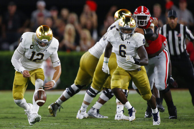 Notre Dame quarterback Ian Book (12) and Notre Dame running back Tony Jones Jr. (6) run after a lose ball in the first half of a NCAA football game between Georgia and Notre Dame in Athens, Ga., on Saturday, Sept. 21, 2019. (Joshua L. Jones/Athens Banner-Herald via AP)
